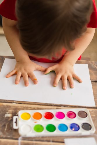 a little boy makes a print of his hands on paper